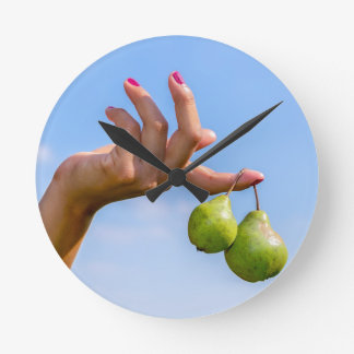 Remettez tenir deux poires vertes accrochantes en horloge ronde