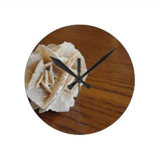 Rose de désert minéral sur la table en bois horloge ronde