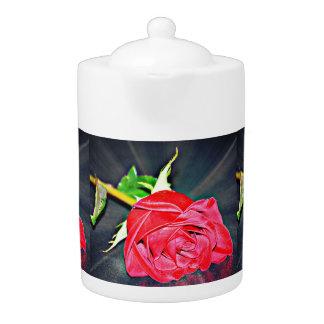 Rose rouge sur le pot de thé noir