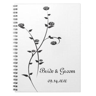 Roses noirs et blancs épousant le carnet de notes