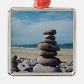 Sculpture en caillou sur une plage ornement carré argenté