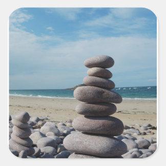 Sculpture en caillou sur une plage sticker carré