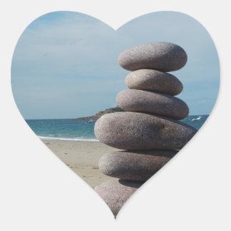 Sculpture en caillou sur une plage sticker cœur