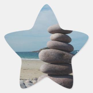 Sculpture en caillou sur une plage sticker étoile