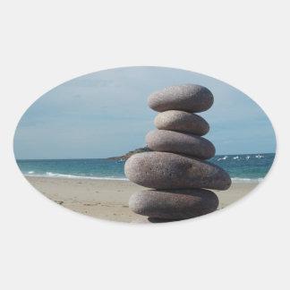 Sculpture en caillou sur une plage sticker ovale