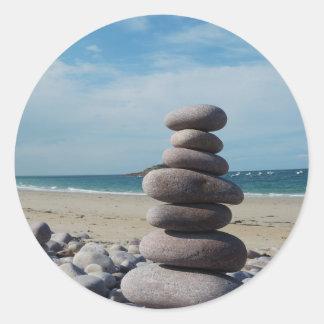 Sculpture en caillou sur une plage sticker rond