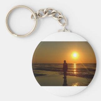 Sculpture en hommes de fer au coucher du soleil, porte-clé rond