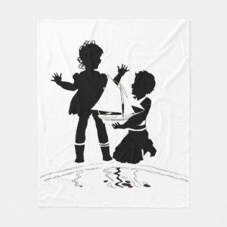 silhouette du bateau de fille et de garçon et couverture polaire