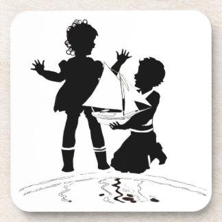 silhouette du bateau de fille et de garçon et dessous-de-verre