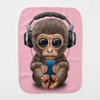 Singe de bébé avec les écouteurs et le téléphone linge de bébé