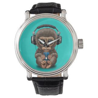 Singe de bébé avec les écouteurs et le téléphone montres bracelet