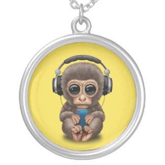 Singe de bébé avec les écouteurs et le téléphone pendentif rond
