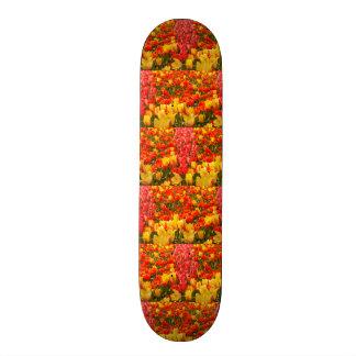 Skateboard la floraison des tulipes en parc sur la planche à