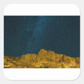 Sticker Carré Ciel nocturne étoilé au-dessus de paysage rocheux