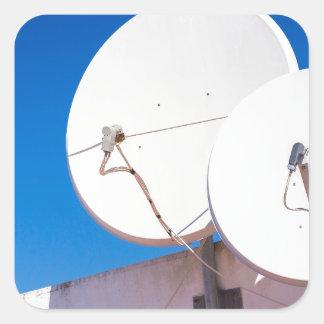 Sticker Carré Deux antennes paraboliques blanches sur le mur de