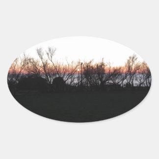 Sticker Ovale Coucher du soleil de mer avec la silhouette
