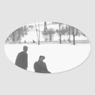 Sticker Ovale Deux garçons tirant deux filles sur des traîneaux