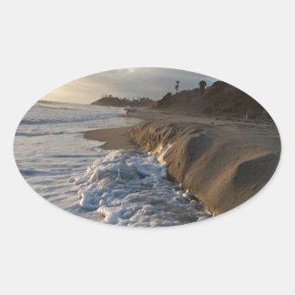 Sticker Ovale Photographie des vagues frappant le sable