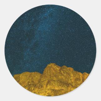 Sticker Rond Ciel nocturne étoilé au-dessus de paysage rocheux