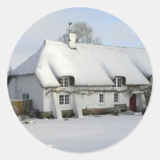 Sticker Rond Cottage anglais couvert de chaume dans la neige