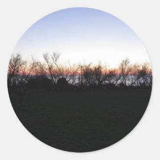 Sticker Rond Coucher du soleil de mer avec la silhouette
