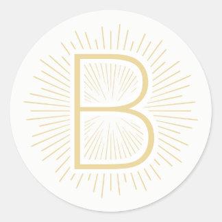 Sticker Rond Rayons brillants d'or de lettre de monogramme d'or