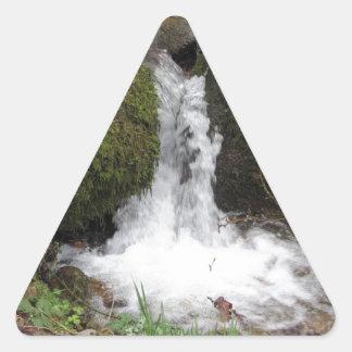 Sticker Triangulaire Peu de cascade par les roches moussues dans la