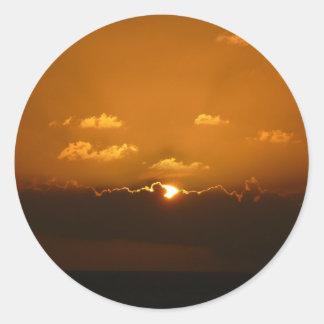 Sun derrière le paysage marin d'orange des nuages sticker rond