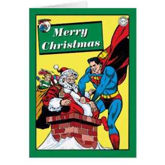Superman aidant le père noël en bas de la cheminée carte de vœux