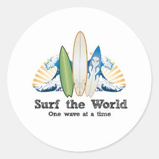 Surfez le monde, une vague à la fois sticker rond