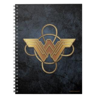 Symbole d'or de femme de merveille au-dessus de carnet