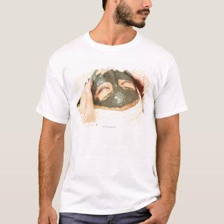 T-shirt Esthéticien qui frotte le paquet de boue sur le
