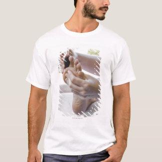 T-shirt Femme obtenant le massage de pied avec la pierre