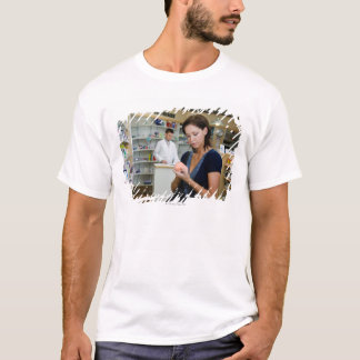 T-shirt Jeune femme regardant la médecine dans la
