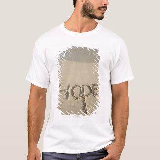 """T-shirt Le sable de """"espoir"""" de mot écrit sur la plage"""