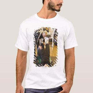 T-shirt L'instructeur aide le client supérieur avec des