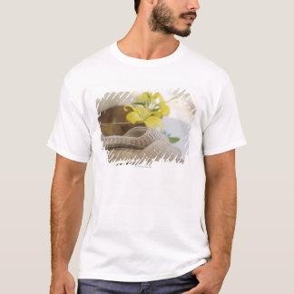 T-shirt Pantoufles près d'une cuvette en bois avec les lis