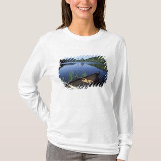 T-shirt Un canoë se repose sur le rivage de peu de long