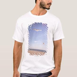 T-shirt une image rêveuse des mouettes volant à la plage