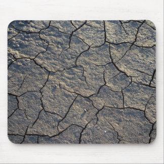 Tapis de souris sec criqué de boue de la terre