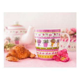 Tasse avec le thé, le croissant et la fleur carte postale
