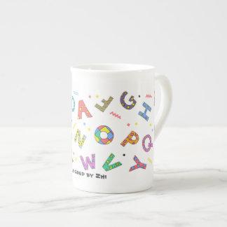 Tasse espiègle de porcelaine tendre d'alphabet