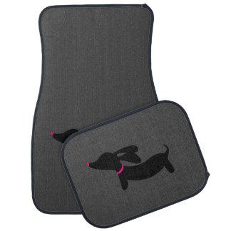 Teckel noir sur les tapis gris-foncé de plancher tapis de sol