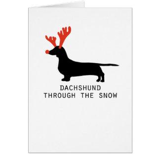 Teckel par la carte de Noël de neige
