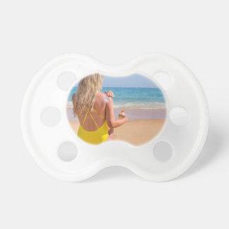 Tétine Fille sur la plage enduisant la protection solaire