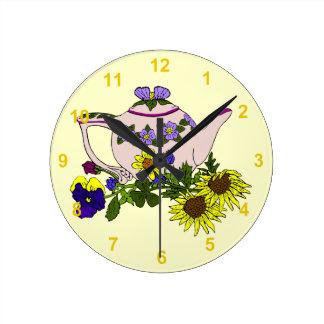 Théière rose avec des fleurs sur le jaune horloge ronde