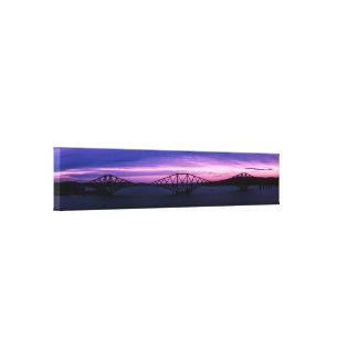 Toile Clôturez en avant le pont en silhouette au coucher