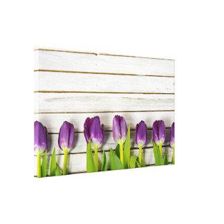 Toile rangée des tulipes pourpres sur le bois