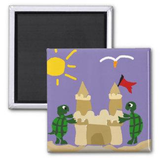 Tortues drôles construisant le château de sable aimant