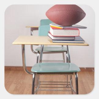 Un bureau d'étudiant avec un football se reposant sticker carré